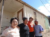 入植当時に入った家の前で。山上桃代さん(左)