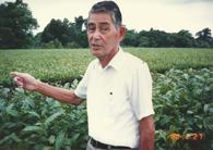 自慢の茶園を指差す山本周作(山本ダリオ茂所蔵、1988年撮影)