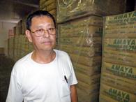輸出用の紅茶袋(60キロ入り)の前で取材に応じる天谷良吾
