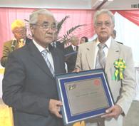 父シゼナンドへの百周年顕彰を受け取るロランドさん(右)