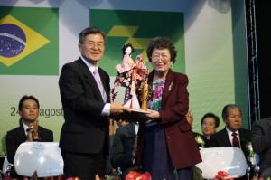稲用副知事(左)から宮崎の工芸品「ひえつき人形」を受け取る高橋会長