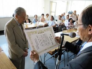 多田さんから表彰状を渡される安良田さん(左)