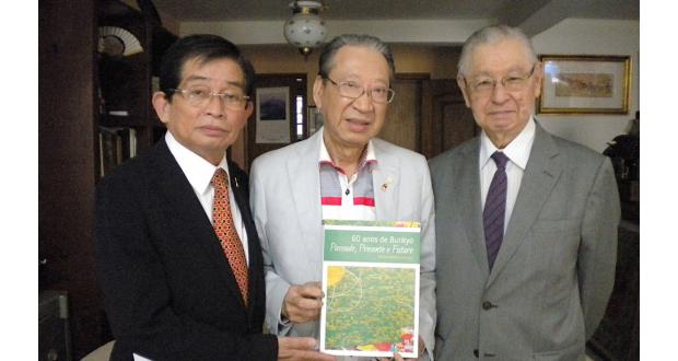 記念誌を手にする木多会長、原田編纂委員長、大原高等審議幹事