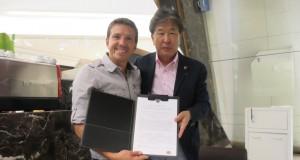 ジュニーニョ会長(左)とサインを交わした竹山理事