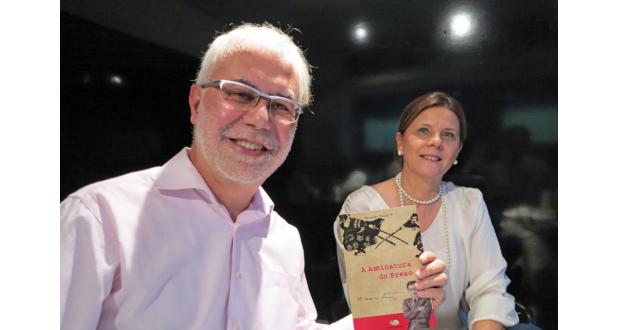 『Assinatura do Preso』を手にする平さんと妻マリアさん
