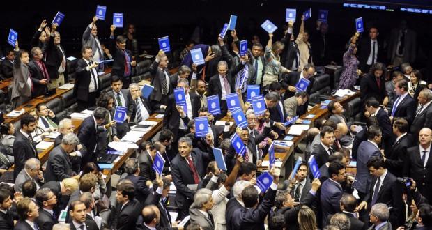 労働手帳を模した青いノートを手に承認反対の意思表示をする下議達(Gustavo Lima/Camara dos Deptados)