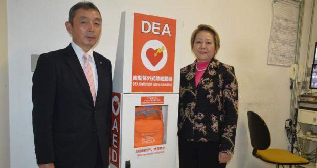 AEDの前で記念撮影する(左から)栗田社長、呉屋会長