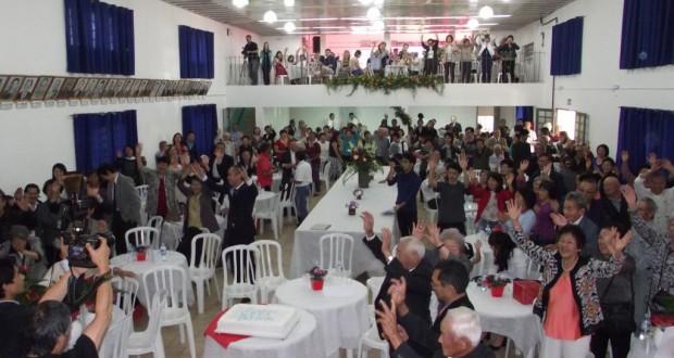 80周年を祝い、万歳三唱をする出席者