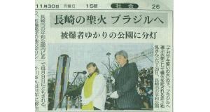 11月30日付長崎新聞。分灯式で種火を受け取った井上祐見(左)と中嶋代表