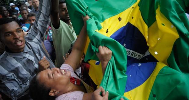 被害者が蜂の巣状態にされた事を穴あきの国旗で表現し、悲しむ参列者達(Fernando Frazao/Agencia Brasil)