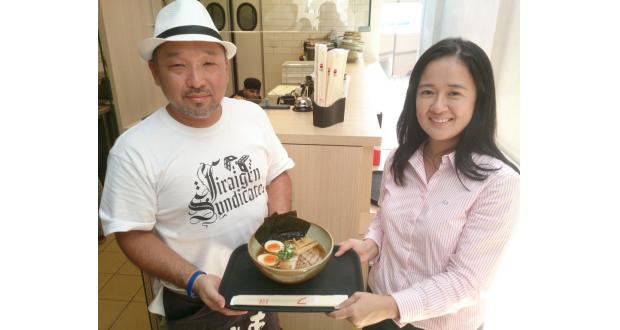 自慢の一品を手にする鯉谷さん(左)とシモーネさん