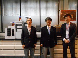 同社の製品を背に的場社長(中)、藤井崇史(左)、中峯弘揮両役員
