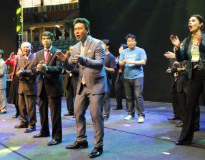 「青年全国大会」の壇上で率先して歌う講師の皆さん(2枚とも伝道本部提供写真)