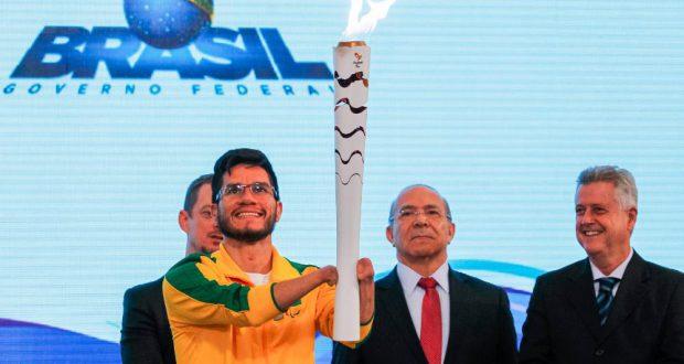 ブラジリアで再点火されたパラリンピック用の聖火を持つヨハンソン・ナシメント(25日、Valter Campanato/Agência Brasil)