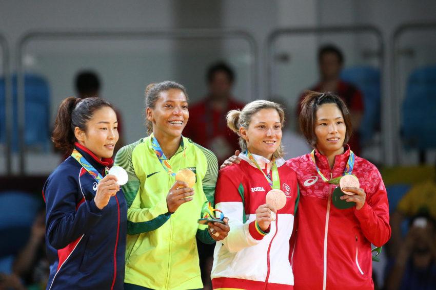表彰台で金メダルを手にする笑顔のラファエラ(左から2人目)。まだこの時の首かけリボンは目新しい。右端は銅の松本薫(Foto: Roberto Castro/Brasil2016)