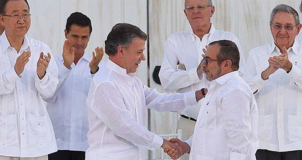 和平合意文書署名式で握手するコロンビアのサントス大統領(左)とFARC司令官ロンドーニョ氏(右)(JUAN PABLO BELLO/SIG)