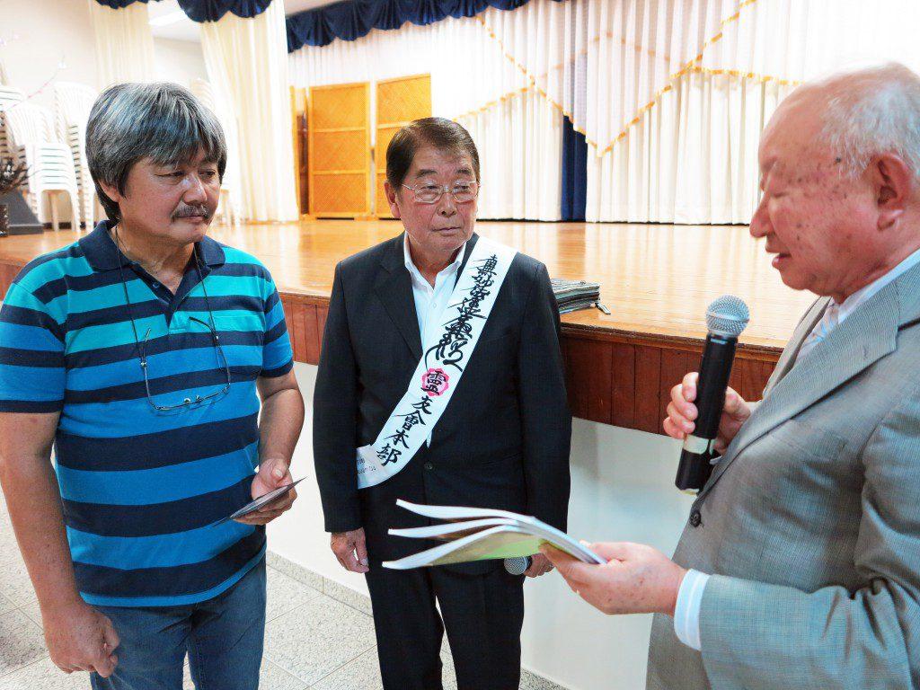 安立会長、安光さんに記念品を渡す本橋幹久団長