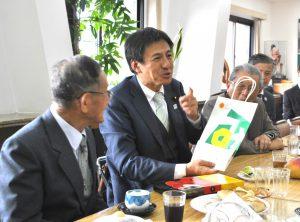 宮崎県人会との交流会にみやげ物を持参し、「いつでも戻ってきて」と県をPRする武井政務官
