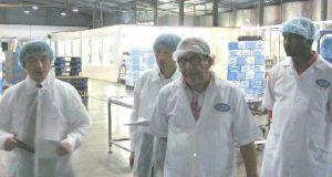 モザンビークのミネラルウォーター工場を視察中。筆者(左)。継松医務官(左から2人目)と