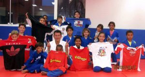 柔道場で寄贈品を受け取った子らと記念撮影する福田さん(提供写真)