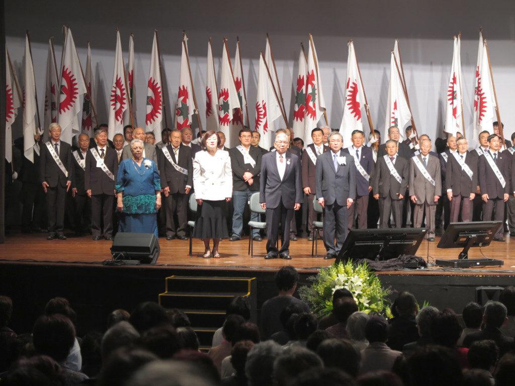 開会式でずらりと並んだ支部旗の前に立つ講師の皆さん