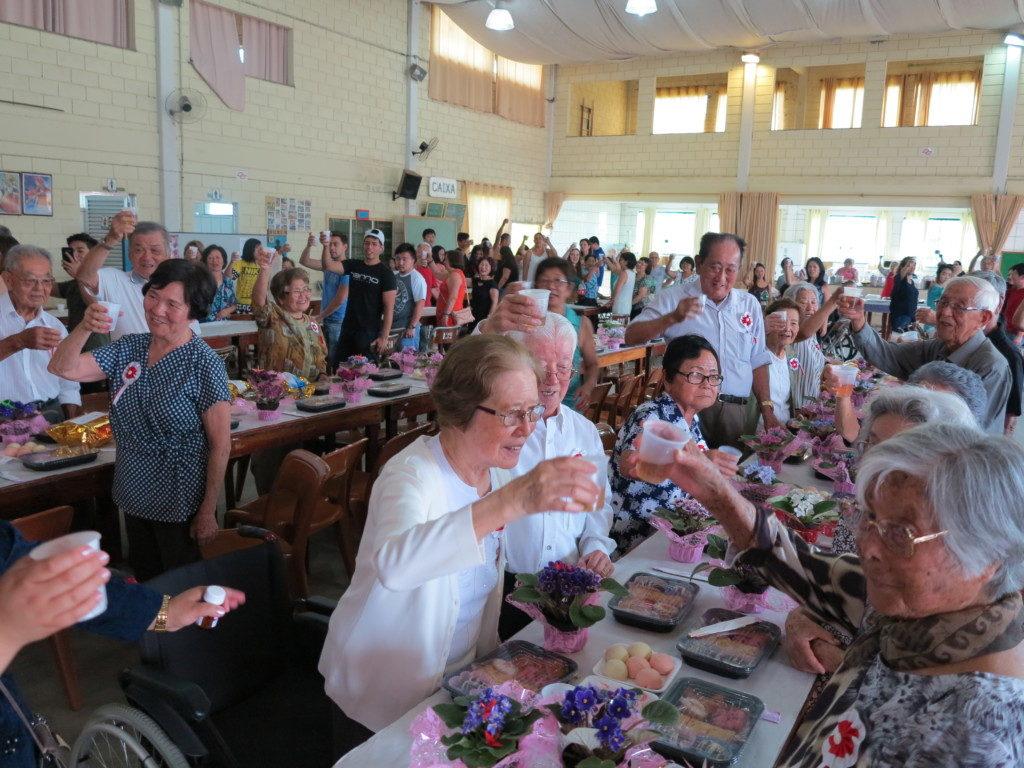 80歳以上の会員に紅白の花勲章と記念品が贈られた