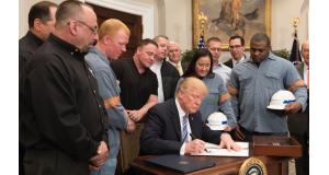 鉄鋼産業労働者に囲まれ、関税措置を定めた宣言書に署名するトランプ大統領(White House)