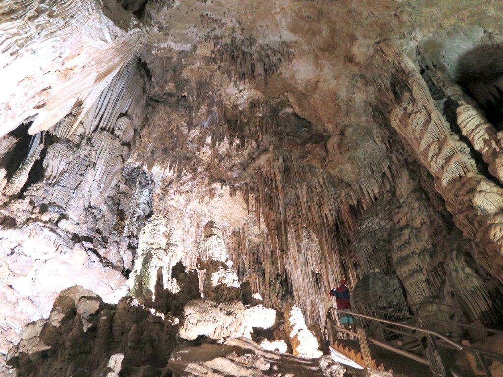 画面右下の階段上部に青年が一人。高い天井に天然のシャンデリアのように釣り下がっている無数の鍾乳石を見つめている