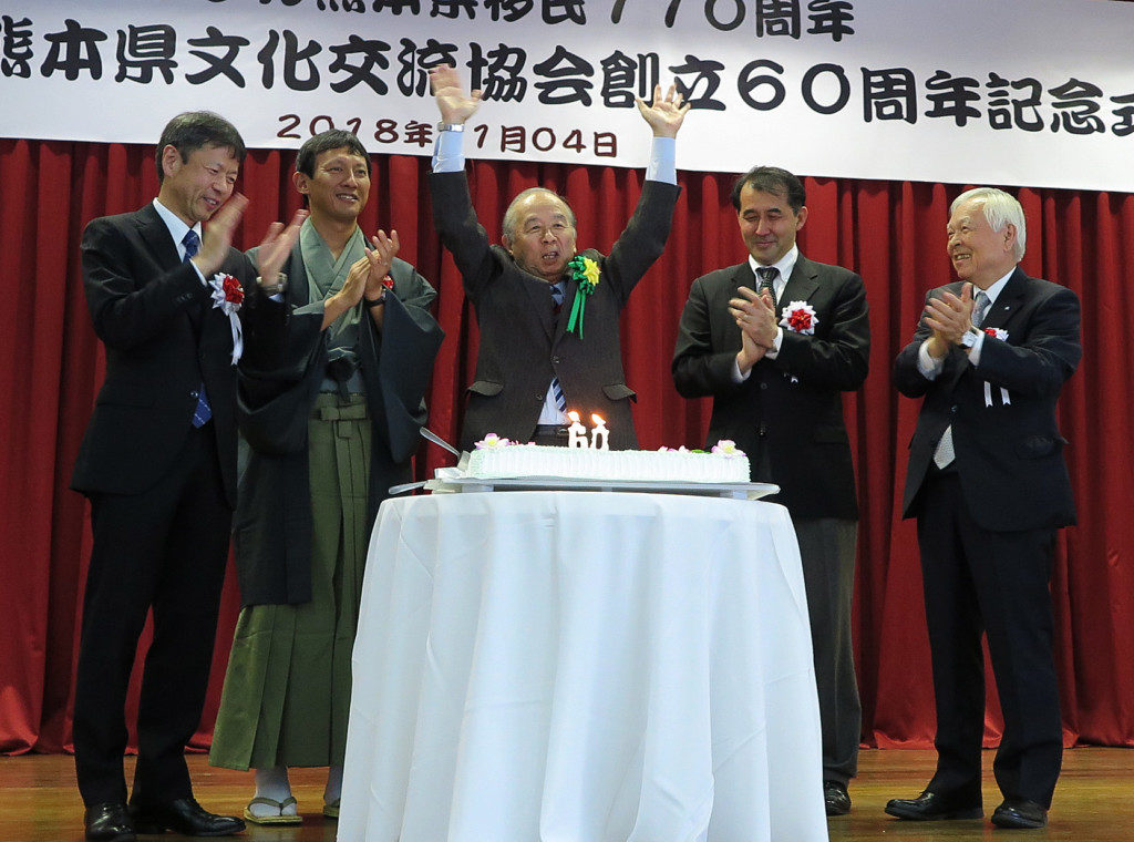 来賓とともにケーキカットをして万歳をする田呂丸会長