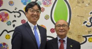 案内に来社した讃井総務委員長、平田事務局長(左から)