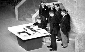 サンフランシスコ平和条約に署名する吉田茂と日本全権委員団([Public domain])