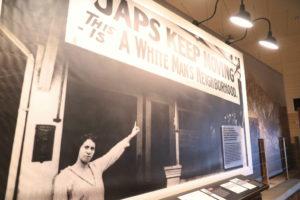マンザナー強制収容所博物館の展示。「日本人は移動せよ。ここは白人の隣人のみ」との看板を指さす白人女性