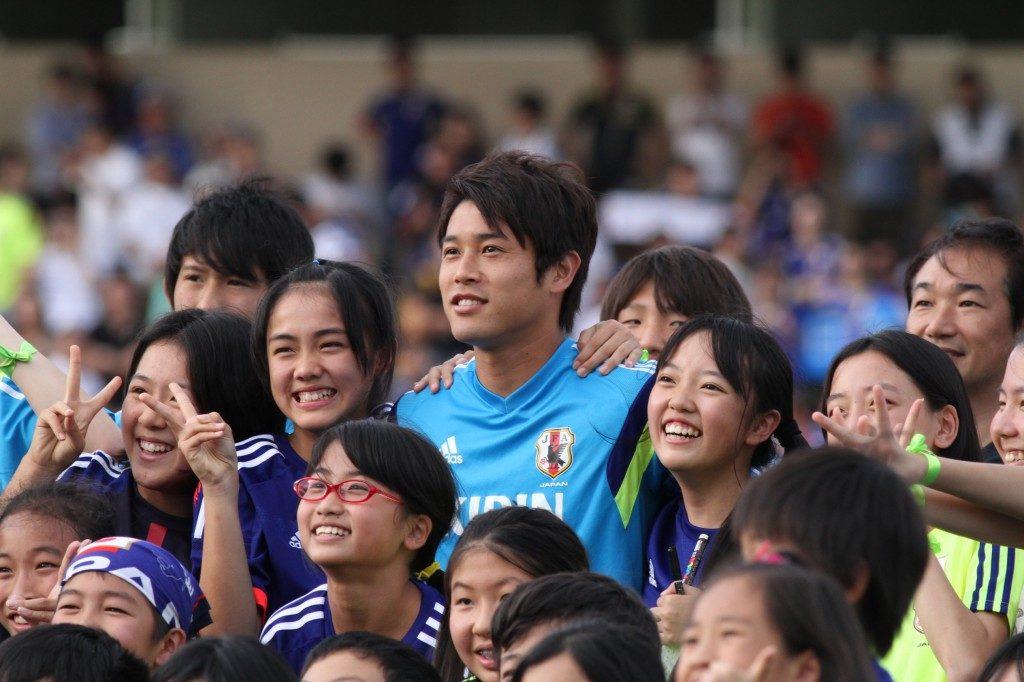 応援に駆けつけた子どもたちとの記念撮影に応じる内田篤人選手(2014年6月サッカーW杯時の公開練習で)