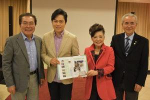 援協から30周年記念史と北島三郎が植樹した木の写真を受け取る松前ひろ子