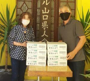 山口県人会会館前で茶そばの受け渡しをする伊藤会長と吉岡会長