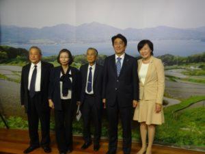 山口県人会で用意したパネルを背に記念撮影する(左から)西村顧問、伊藤事務局長、要田会長、安倍総理、昭恵夫人
