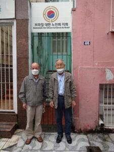 ボン・ヘチーロ地区の大韓老人会事務所入口に立つ金進卓さん(右)と鄭夏源さん