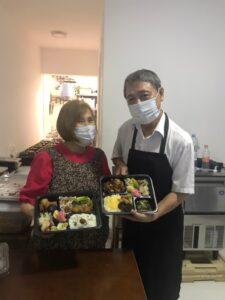 仲良く弁当をみせる夫婦(左からマルガリータさん、原口さん)