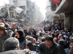 爆撃を受け、国連の救援物資を待つ人々(2014年2月17日、シリア国首都ダマスカス市ヤルムーク地区、Foto: UNRWA)