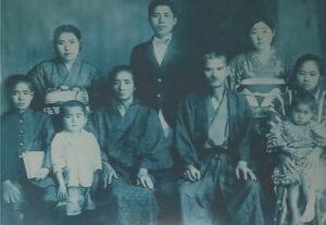 1937年―安慶名家の家族写真。次男信綱を膝にのせているのが篤成の妻カマド。左側で、白いシャツを着ている子が長男篤政。前列中央が篤成の父金次郎、その左母マツ、左端篤成の弟恒信(三男)。後列中央が篤成の兄篤信(長男)、その左が篤成の妹サダ、右がカマドの友人