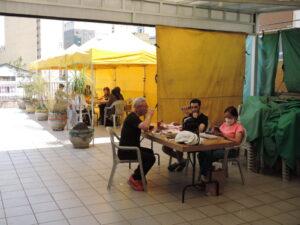 テーブルの間隔をあけて屋上で飲食を楽しむ参加者